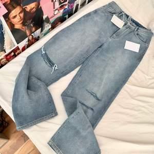 Snygga jeans med en rak passform.  - Vävt tyg utan stretch - Dekorativa hål på knäna - 5-ficksjeans - Innerbenslängd: 85 cm i storlek 38