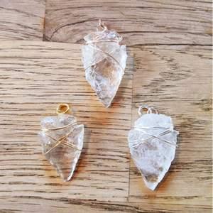 Pilspets-format hängsmycke av kristallkvarts. Cirka 3-4 cm långt.   Går att få i färgerna: silver, guld och rose. Färg och form på kristallen kan variera lite då det är en naturlig sten, och formen är huggen för hand.   Skickas i vadderat kuvert via postnord.
