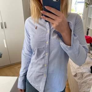 Säljer denna ljusblåa skjorta från Ralph Lauren i storlek 4 (vilket typ motsvarar 34/36). Den har en liten fläck på sig vid högra nyckelbenet (se bild två). Annars är den i gott skick.  En fraktkostnad tillkommer om inte annat är överenskommet.