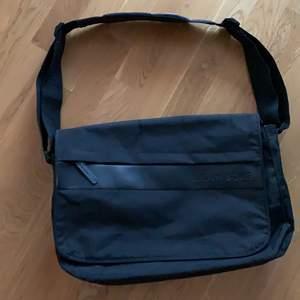 Större väska än vad det ser ut och man får plats med en massa olika saker då den har många praktiska fack. Har reflex på bandet. Bandet går också att ändra storlek på.
