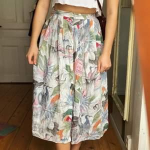 Superfin kjol med knappar fram och en ficka på ena sidan. Köpt secondhand och har ett roligt mönster med lite fäglar, blad och frimärken. Står storlek 40 men lite liten i storlek.
