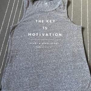 """Köpt på H&M sport, storlek S, stretchigt material och inte varmt, fin nyans av grå och även ett citat där det står """"the key is motivation"""". Används till träning och varma sommar dagar om man vill!!"""