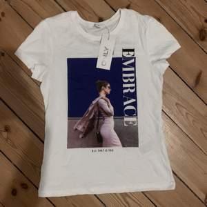 """T-shirt med tryck och texten """"embrace"""". T-shirten är aldrig använd och prislappen sitter kvar. Strl S. Skriv ett pris som känns rimligt för dig vid intresse! Hör av dig för fler bilder eller frågor!🤍"""