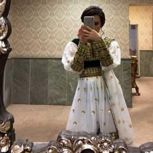 Fint puffig afghanska kläder som är i färgen grön och vit