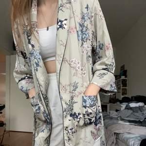 Jättefin silkes kimono från Ella M! Helt oanvänd och i perfekt skick, har ett band och två fickor på framsidan. Kan bäras hursomhelst, som pyjamas men också vardag, eller varför inte över bikinin? Superfin och unik med finaste mönstret! 💚