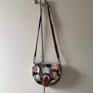 Säljer denna som är köpt i thailand för att det inte används längre, en söt väska med elefanter på med ett brunt axelband. Köparen står för frakten.
