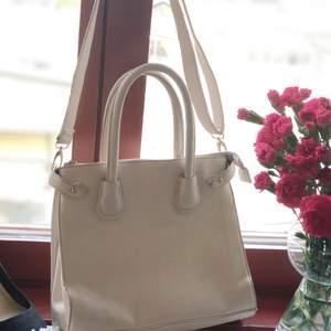 medelstor krämvit väska med olika fack och två fickor med dragkedja! (finns ett litet svart märke på baksidan) Leverans: kunden står för kostnaden