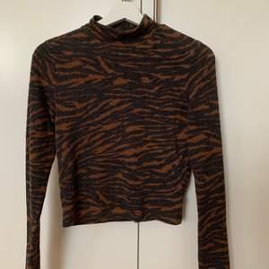 Tight tröja med brun-grått djurmönster. Har en liten/låg polokrage men inget som ger strypkänsla. Den är inte croppad men inte heller lång, alltså slutar den perfekt till högmidjade byxor utan att behöva vikas in! Skriv vid intresse💗