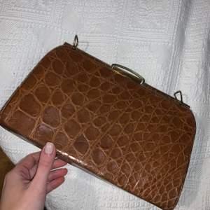 Trendig vintageväska med guldiga detaljer och innerfack, perfekt storlek som rymmer det man behöver. Band saknas men finns hällor att fästa annat band eller kedja!💕