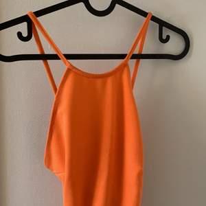 Orange linnebody i storlek S från NLY ONE. Ryggen är öppen, och banden korsas.