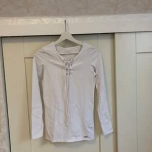 En kort vit klänning från GUESS med snörning upptill. Använd typ 2-3 gånger. Kan även ha den till jeans som en längre tröja. Superskönt material, väldigt mjukt. Figursydd