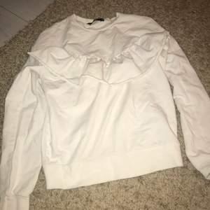 En vit långärmad tröja med volanger på i storlek xs ifrån bikbok. Köparen står för frakten!