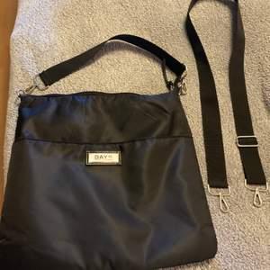 En svart Day et väska med rött innefoder. Två  fickor på insidan och ett större fack på utsidan!  Nyskick- endast använd ett fåtal gånger!