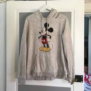 En gråmelerad hoodie med Musse Pigg på. Tror att trycket var lite utnött från början men också att det slitits ut lite till vid användning. Färgen är lite lite ljusare än på bilden då den är nytvättad.  Köpt på H&M i storlek XL. Säljer pga att den inte används. 80kr + frakt.