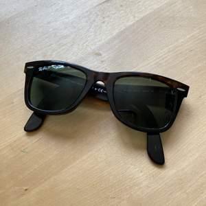 Begagnade Rayban Wayfarer solglasögon. Polariserade glas, så funkar både på havet och i skidbacken. Storlek standard/mindre. Inga repor på glasen men ngt slitna långt bak på skalmarna. Mörkbruna. 140mm, lins 50, brygga 22.  Skalmarna är börja efter mitt huvud/mina öron, men går lätt att böja om på en glasögonaffär. Nypris ca 1400:-, (köpta på Ray-Ban butik i New York)