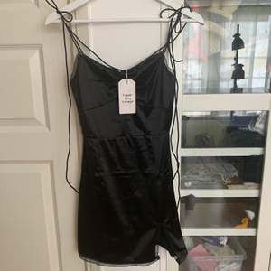 Svart miniklänning med slits vid låret! Den är i nyskick med märkeslappen kvar. ‼️ Köparen står för frakt ‼️