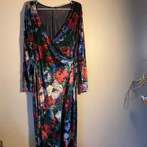 En vadlång blommig omlott klänning ifrån Zara. Klänningen går att öppna upp helt. Materialet på klänningen påminner om siden