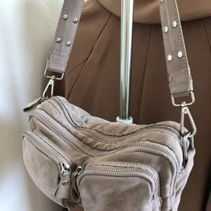 Väska i mockaimitation från ginatricot. Fint skick bortsett från en liten defekt på bandet (se bild 3), denna kan dock lätt bytas ut.