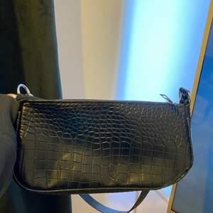 Svart väska, one size. Aldrig använd. Säljer för 70 kronor + frakt (man kan stoppa in dragkedjan som sticker ut åt sidan)