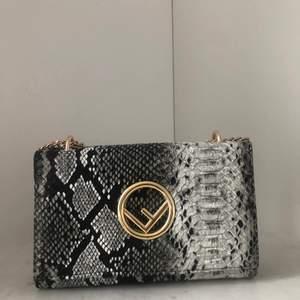 Svart vit väska med orm mönster och guld detaljer