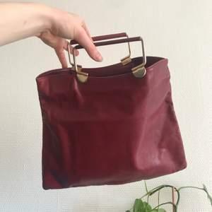 Röd handväska i äkta skinn med dragkedja och inneficka.