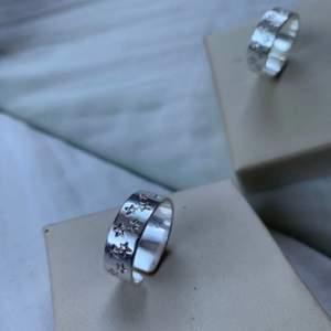 Silverring med stjärnmönster i justerbar storlek. Egendesignad ring för att uppmärksamma djur som dör till följd av tjuvjakt. Tillverkad för hand i Sverige