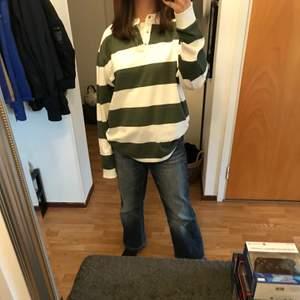 En randig långärmad tröja i färgerna mörkgrön och vit. Den har även en krage upp till och knappar (bild 3). Köpt på Lager 157 och endast använd ett fåtal gånger. Bra skick dock en liten liten liten fläck på den men den syns knappt (se bild 2).