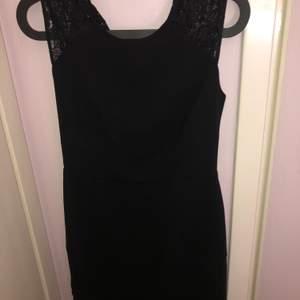 En fin svart sofistikerad klänning som fortfarande har prislapp och helt nytt skick. Med spets på axlarna