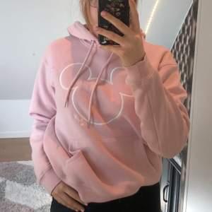 En super fin och skön rosa hoodie med vitt kontur av Musse pigg!