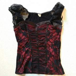 Rött-svart plagg i korsett-stil med fina genomskinliga ärmar på axlarna. Sitter fint på kroppen! Pris är inklusive frakt 😊