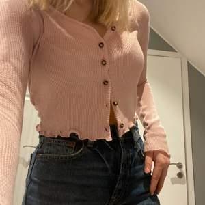 Rosa kofta i tunt, stickat material. Går att använda som både tröja eller kofta.