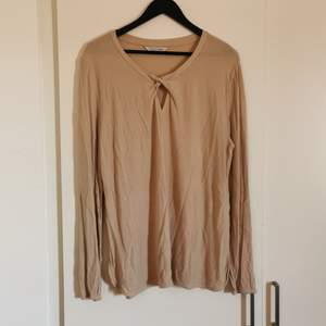 A comfy shirt that doesn't sit tight with long sleeves and cuts on the side. A nude color with a detail in front. Works as a yoga shirt too. 😋