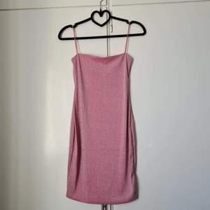 Rosa glittrig klänning. Helt oanvänd. Kom utan tag dock.   Storlek S men är stretchig så kan passa mindre och större.  150 kr +frakt