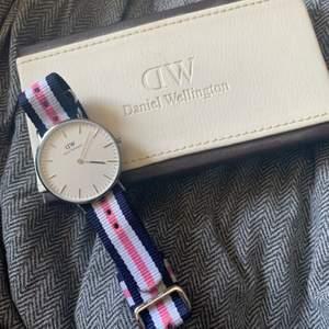 En fin och nästan oanvänd klocka från Daniel Wellington! Den är marinblå och rosa med silver detaljer. Batteriet behövs fixas då den har stannat, annars är den i helt nyskick och bara legat i förpackning. Nypris: 1200kr