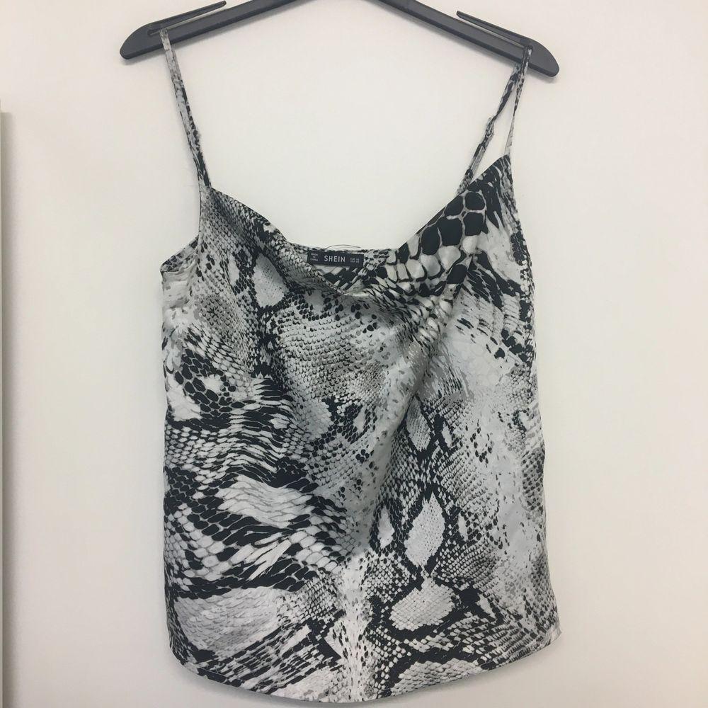 Ormönstrat linne i grått, vitt och svart. Aldrig använd.. Toppar.
