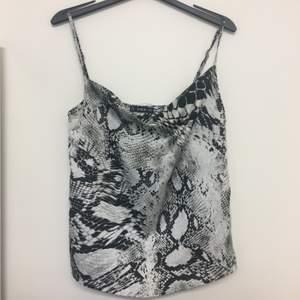Ormönstrat linne i grått, vitt och svart. Aldrig använd.