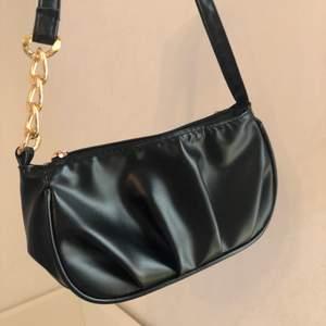En söt liten svart väska med fina gulddetaljer som är köpt för en månad sen och inte har kommit till användning. Köpte den för 140 och säljer den för 90. Kunden står för frakten. Den är jätte fin och passar till de flesta klädesplagg. Skriv till mig för fler bilder, skickar gärna🥰