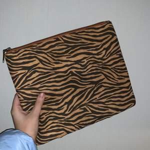 En väska/clutch med tigermönster. Aldrig använd