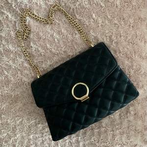 Säljer en helt oanvänd svart och guld mindre väska, alla detaljer på den är i guld. Papper är kvar inuti från när den köptes. Säljer för 120 kr. Köparen står för frakten!