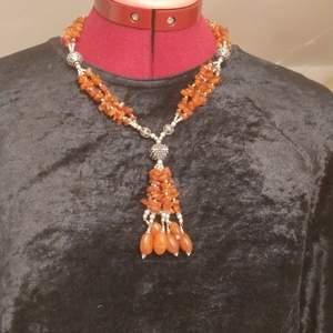 Halsband av karneol med hänge i form av tofs. Längd cirka 45 cm, justerbart.