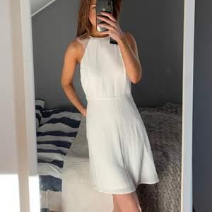 Vit klänning med öppen rygg, aldrig använd med lappar kvar. Perfekt till student eller skolavslutning och till sommaren!