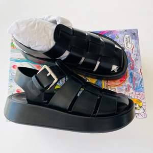 Oanvända sandaler i svart skinn.