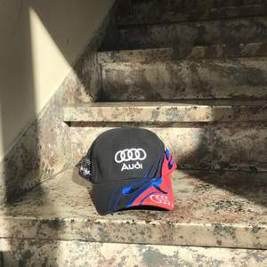 """En keps med  """"Audi"""" som står på den. Den är justerbar och finns bara ett 1x."""
