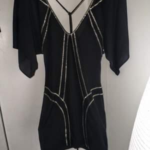 Elegant, kort klänning med guldpaljetter. Snöre som man kan placera och ha den hur man vill. Använd en gång. Stl U men passar stl 34/36. Väldigt vacker och exklusiv klänning med bästa kvalitén. Kan pruta ner priset vid snabb affär.