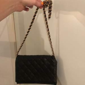 Detta är en väska i svart fake skinn. Bandet är i guld och svart. Den är En knapp är lite dålig men den funka