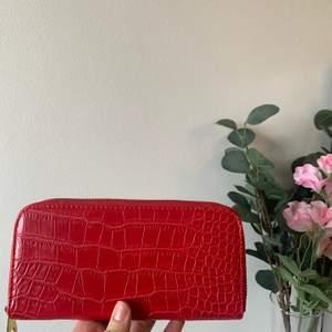 Röd elegant plånbok som innehåller många fack. Helt oanvänd, står inget märke på!