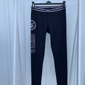 Ett par nästintill oanvända träningstights ifrån Svea i en marinblå färg med vit text på höger ben.