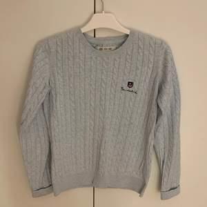 En ljusblå kabelstickad tröja i väldigt fint skick. Använd endast ett fåtal gånger. Köpt på MQ för 600kr.