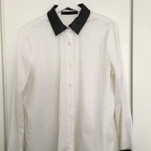 Vit bomullsskjorta med svarta lammskinnsdetaljer kring kragen och ärmar. Använd fåtal gånger, i mycket gott skick. Storlek EU 38  Nypris: 2300 SEK