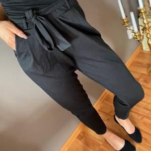 Svarta supersköna byxor i stretchigt material. Är 173cm lång och de slutar lagom vid ankeln. Använda en gång! Knyts med skärp i midjan och passar XS-S